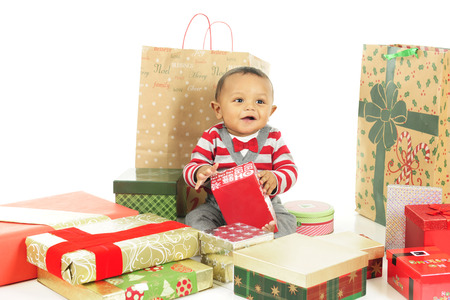 dressed up: An adorable, dressed up baby boy enjoying the wrapped gifts that surround him.  On a white background.