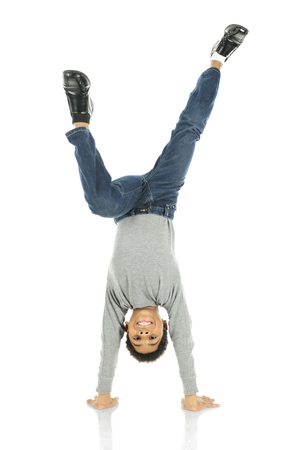 An elementary boy deslightedly standing on his hands.  On a white background. Stock Photo