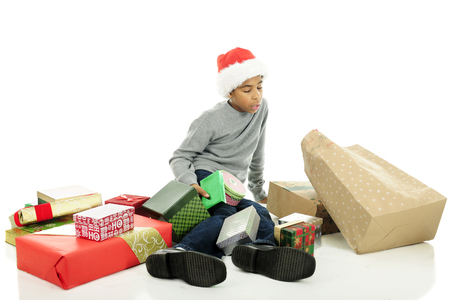 closed ribbon: An elementary boy who has fallen while carrying a many Christmas gifts.  Hes now on the floor with wrapped gifts all around.  On a white background. Stock Photo