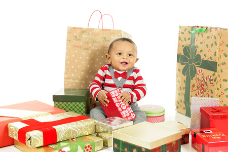 dressed up: An adorable, dressed up baby boy obviously loving being surrounded by lots of wrapped gifts.  On a white background.