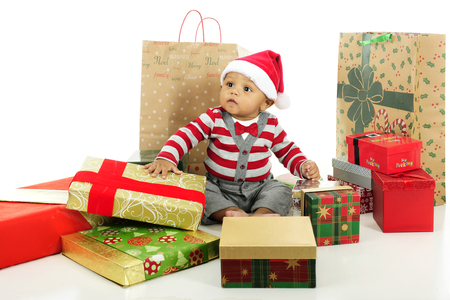 An adorable baby looking a bit overwhelmed by the assortment of wrapped gifts surrounding him.  On a white background. Stock Photo