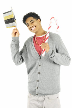 tipping: A tall young man tipping his sparkly New Years Eve hat while holding a giant Christmas candy cane.  On a white background.