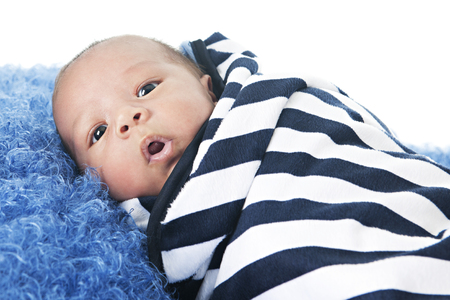 swaddled: A biracial newborn swaddled in a black and white striped blanket.  On a white background.