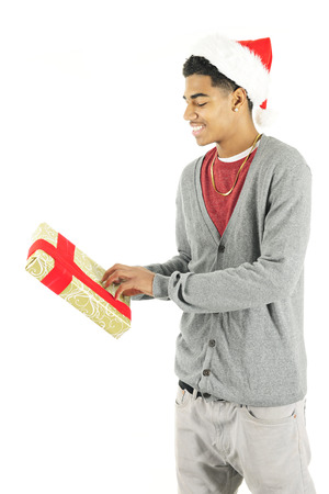 A slim young man in a Santa hat happy but curiously fingering a Christmas gift.  On a white background. Stock Photo