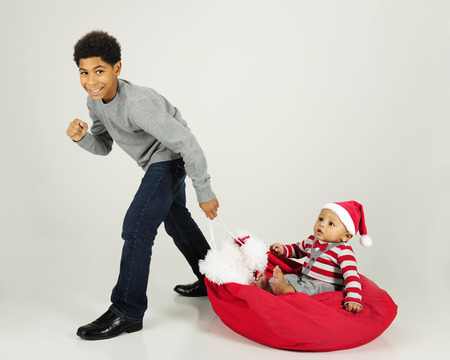 handome: A handome African American boy happily pulling his baby brother along the floor on Santas sack.  On a gray background. Stock Photo