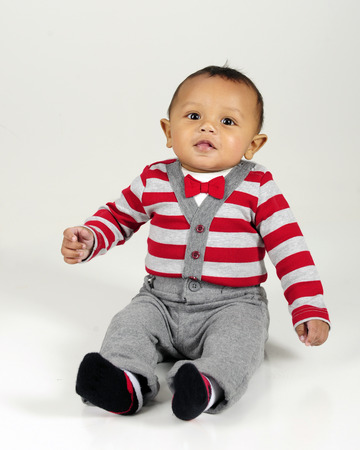 red cardigan: A handsome young baby sitting in his striped sweater and bow tie.  On a gray background.