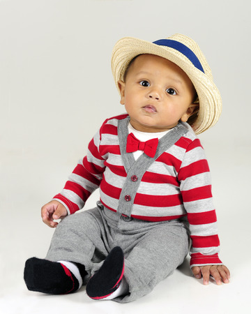 fedora: An adorable baby born sitting in his red and gray striped sweater, red bow tie and fedora.  On a gray background.