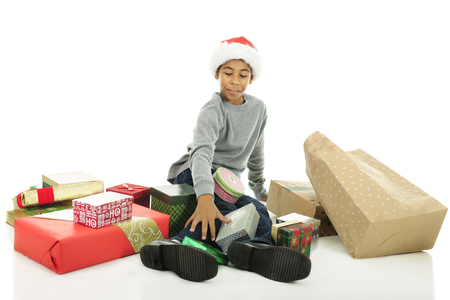 stash: An elementary boy sitting on the floor while happily looking over his stash of unopened Christmas gifts.  On a white background.