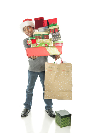boy jeans: A handsome elementary boy delightedly carrying a large stack of wrapped Chrstimas gifts.  On a white background. Stock Photo
