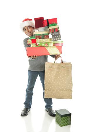 niño parado: Un muchacho elemental apuesto llevar con deleite una gran pila de regalos envueltos Chrstimas. Sobre un fondo blanco.