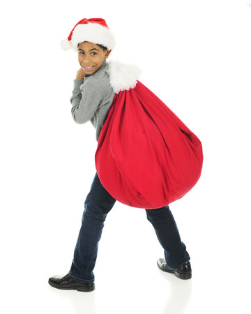 looking at viewer: An elementary boy looking over his shoulder at the viewer as he hauls Santas sack on his back.  On a white background.