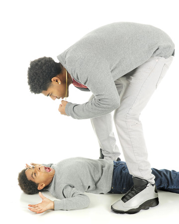 overpowered: Two brothers fighting.  The tall older teen straddles and stands over his elementary brother who is surrendering from his position flat on his back.  On a white background.