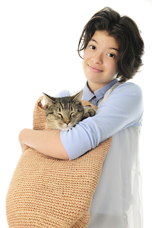 comforted: An attractive young teen holding her sleeping cat in a tan woven shoulder-strap bag. Focus on the girl.  On a white back ground.