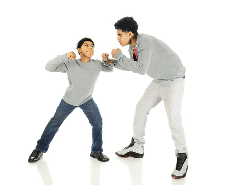 sibling rivalry: An elementary boy raising his fists towardsr his much tallerl older brothers.  On a white background.