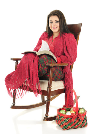 A beautiful teen girl smiling up from reading the Christmas Story.  Shes snuggled in her pajamas under a red blanket while sitting in a rocking chair.  On a white background.