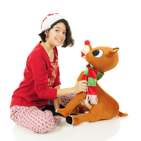pj's: An attractive teen girl  in her pajamas smiling at the viewer as she holds on to a large stuffed Rudolph.  On a white background. Stock Photo