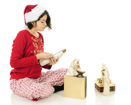 nativity set: An attractive young Hispanic admiring a shepherd from her Nativity set, with the others set up nearby.  Shes wearing Christmas pajamas and a Santa hat.  On a white background.
