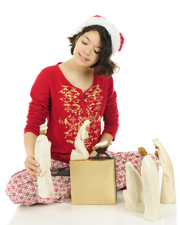 nativity set: A young teen Hispanic happily checking out and setting up a Nativity set.  Shes wearing her Christmas pajamas and a Santa hat.  On a white background. Stock Photo