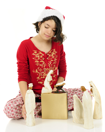 pj's: A young Hispanic teen arrangting the Nativity characters while wearing her pajamas and a Santa hat.  On a white background.