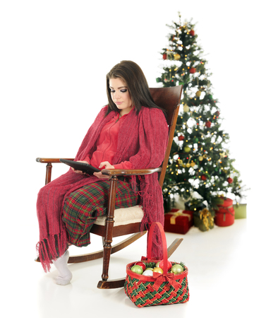 pj's: A beautiful teen girl snuggled up in her pajamas and a blanket,  using her ipad in a vintage rocking chair.  A basket of ornamets are by her side and a dlighted Christmas tree is behind her.  On a white background.