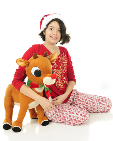 pj's: A pretty Hispanic teen hugging a stuffed Rudolph in her pajamas and a Santa hat.  On a white background.