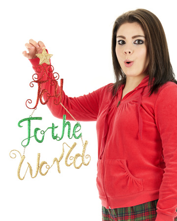 Close-up of an expressive teen girl in her pajamas holding up a glittery Joy to the World decoration for the viewer to see.  On a white background.