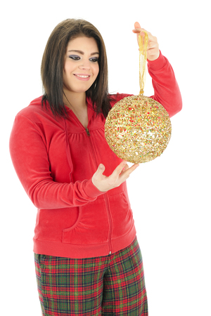 admiring: A beautiful teen girl in her pajamas admiring a giant, golden Christmas bulb.  On a white background.