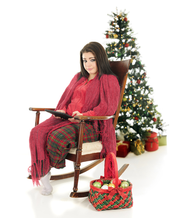 basketful: A beautiful teen girl snuggled up in her pajamas and a blanket while working on her ipad.  A basketful of ornaments are nearby with a decorated tree behind her.  On a white background.