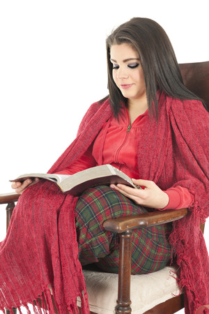 pj's: A beautiful teen girl cozied in her Christmas PJs and a red blanket in a rocking chiar reading her Bible.  On a white background.