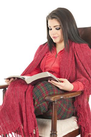 leer biblia: Una muchacha adolescente hermosa cozied en su pijama de Navidad y una manta roja en un chiar balanceo leyendo su Biblia. Sobre un fondo blanco.