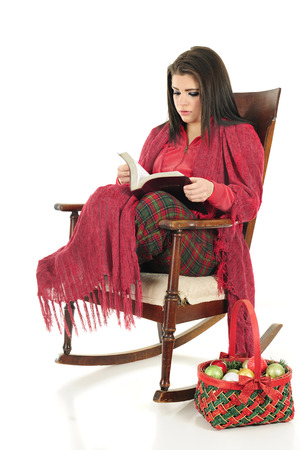 pj's: A beautiful teen girl cozied up in her PJs and a blanket as she reads her Bible in a rocking chair.  A basket of Christmas bulbs on the floor nearby.  On a white background.