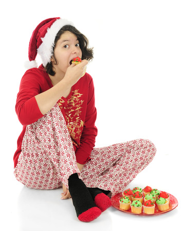looking at viewer: An attractive teen girl looking at the viewer as she pops a whole miniature cupcake in her mouth.  Shes sitting on the floor in Christmas pajamas and a fluffy Santa hat.  On a white background.