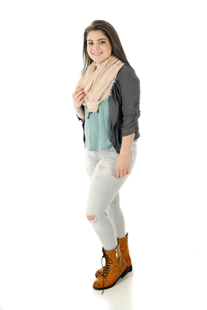 holey: A beautiful teen girl happily standing in her holey jeans, eternal scarf and lace-up, zipper-up boots.  On a white background.