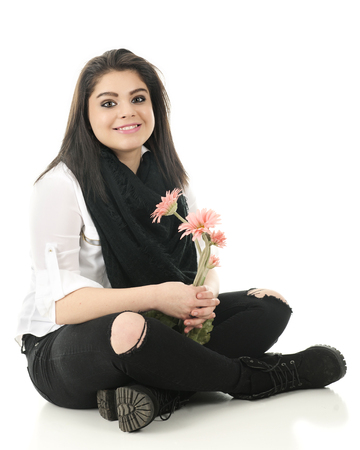 holey: A beautiful teen girl happily holding a small bouquet of pink flowers as she sits cross-legged on the floor in a black and white outfit.  On a white background.