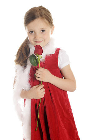 A beautiful elementary girl in red, happily holding a  red rose bud.  On a white background. photo