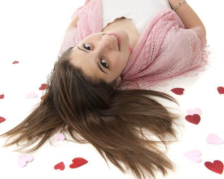 sparkly: A beautiful teen girl on her back, looking up at the viewe.  Her head is surrounded by sparkly red and pink hearts.  On a white background.