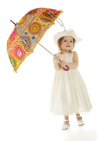 dressed up: A beatiful toddler dressed up in white carrying a brightly colored parasol.  On a white background. Stock Photo