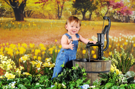 A beautiful baby boy happily playing with a rustic water pump among yellow daffodils. photo