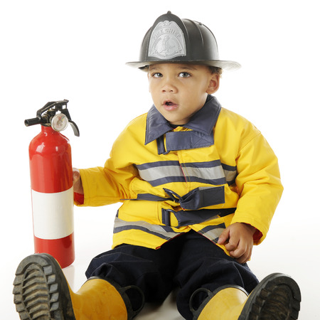 looking at viewer: An adorable preschool fireman looking at the viewer while holding an extinguisher.  On a white background. Stock Photo