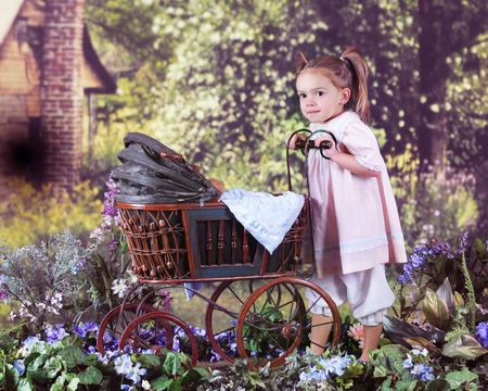summer dress: An adorable preschooler pushing her teddy in an antique doll carriage toward a rustic old homestead on a bright summer day. Stock Photo