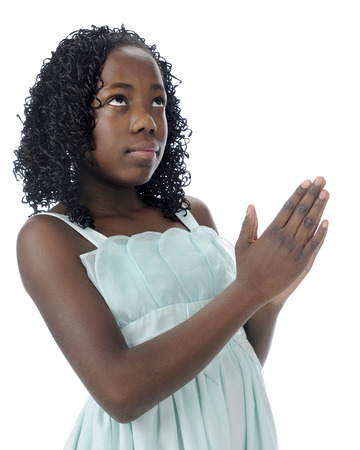 clasped hands: A beautiful preteen looking heavenward as she prays with clasped hands.  On a white background. Stock Photo