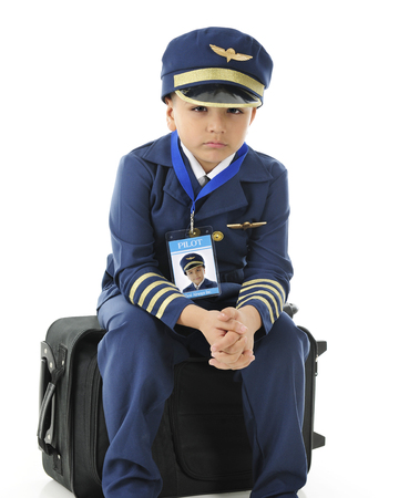 An elementary airline pilot sitting on his suitcase, bummed because his plane has been delayed.  On a white background.