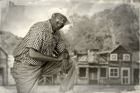 western town: A tall, senior black cowboy in an old western town. Stock Photo