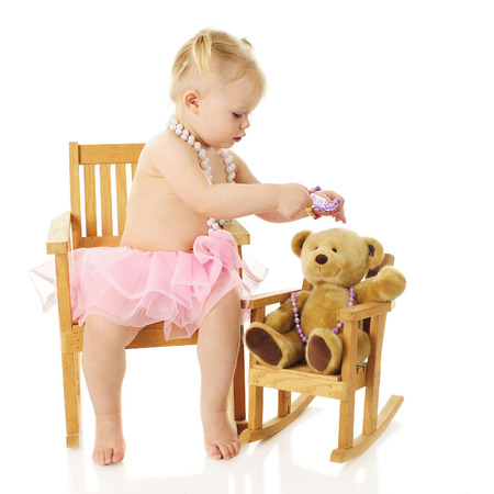 lookalike: An adorabel 2-year-old wearing a pearl necklace and tutu placing a bracelet crown on her Teddy bears head.  Both child and bear are in look-alike rockers.  On a white background. Stock Photo