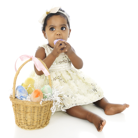 kids dress: An adorable, dressed up baby girl prepared to eat a whole egg from her Easter basket which sits by her side.  On a white background. Stock Photo
