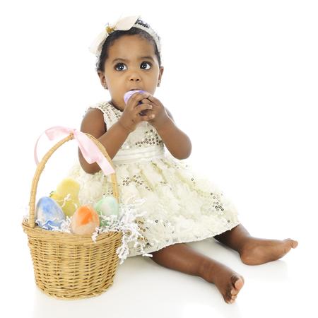 ni�os sentados: Un vestido encima de la muchacha adorable, beb� preparado para comer un huevo entero de su cesta de Pascua, que se sienta a su lado. Sobre un fondo blanco.
