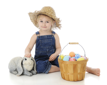 farm girl: An adorable preschool farm girl happily petting a bunny with a fruit basket full of colorful eggs.  On a white background.