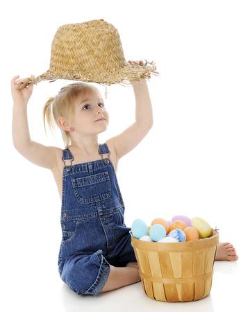 """canasta de frutas: Un preescolar """"chica de campo"""" adorable mirando a su sombrero de paja hecha jirones. Ella se sienta detr�s de una cesta de fruta llena de huevos de Pascua coloridos. Sobre un fondo blanco. Foto de archivo"""