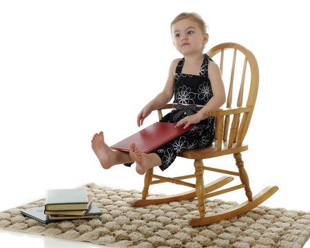Een mooie kleuter zoekt tevreden in haar rocker, met een boek op haar schoot en een stapel van anderen door haar voeten. Op een witte achtergrond. Stockfoto