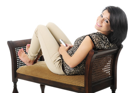 A beautiful teen gir smiling over her shoulder at the viewer with her i-pad on her lap.  On a white background.
